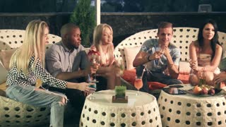 Group of happy trendy multiracial friends enjoying an evening drink together on stylish modern furniture on an outdoor patio