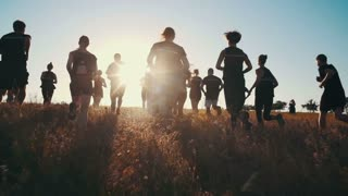 Group of people running on a field in sunset, slow motion