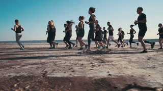 Group of people running on the beach, slow motion