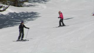 Group Of Skiers Glide Down Easy Hill, Pass Camera