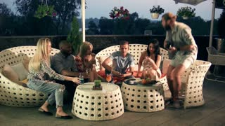 Group of young multiracial friends laughing and drinking on trendy modern furniture on an open-air patio while a male friend prepares to take a photograph of them enjoying themselves