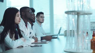 Group of young people students in white coats in chemistry lab listening the lector. Pharmacy classes concept. Footage with copy space