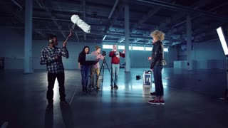 Group of young people with camera on tripod, laptop and boom mic setting gear for shooting scene with man in hat and caucasian young girl in leather jacket standing and playing role or giving