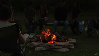 Group Sits Around Campfire At Dusk