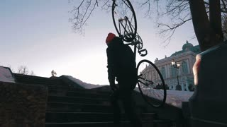 Guy carrying a fixed gear bike and climbing up the steps,super slow motion