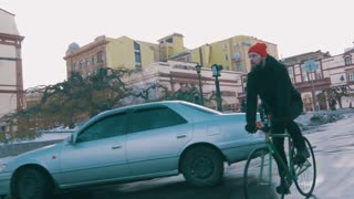 Guy riding fixed gear bike on the road in city, 4k