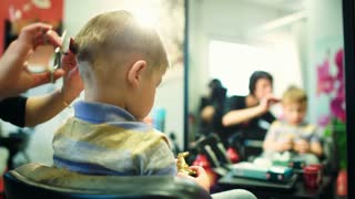 Hairdresser cutting boys hair while he playing with a toy. Back view with defocused reflection in the mirror