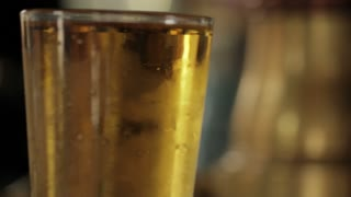 hand passes beer in front of tall glass, collects pay off bar