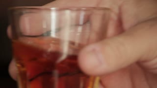 hand sets down whiskey glass