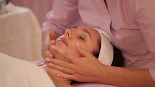 Hands of professional masseuse massaging woman's face at beauty spa