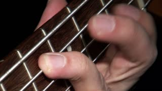 Hands Playing Neck of Bass Guitar