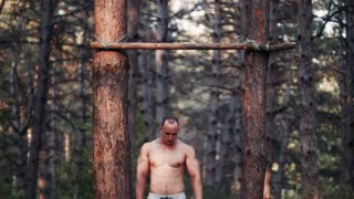 Handsome and strong bodybuilder doing pull-ups on handmade horizontal bar in forest