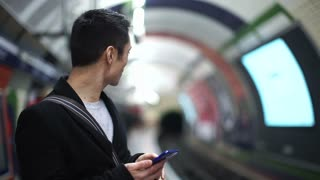 Handsome asian man on his phone at a train metro station