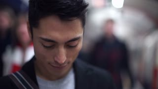 Handsome asian man smiling to camera at a train station