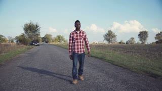 Handsome black man in plaid shirt and blue jeans walks down lonely country road