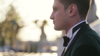 Handsome brunet bridegroom in black wedding suit and bow tie comes up to beautiful bride and gives her a kiss. Wedding portrait. Bright sunset. Atmosphere of love. Outside shooting, close up view.