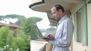 Handsome businessman working on laptop and standing on balcony