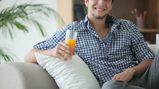 Handsome guy relaxing on sofa drinking juice and smiling
