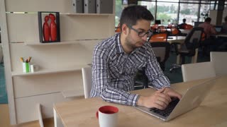 Handsome man mixed race typing on the computer at his working place. On the background colleagues work with laptop. Brunet with eyeglasses on his face. Behind young male wooden sh