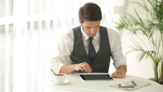 Handsome young man sitting at table and using touchpad