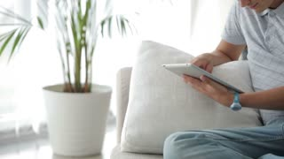Hansome young man sitting on sofa using touchpad looking at camera and smiling