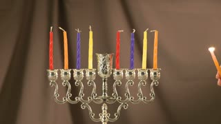 Lighting menorah with Hanukkah candles