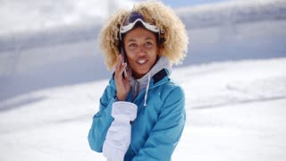 Happy adult in snowsuit with cell phone