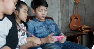 Happy asian child playing tablet computer and cell phone together .