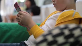 Happy Asian child using a digital cellphone at home .