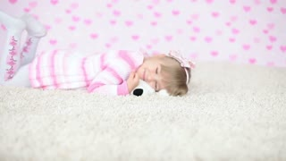 Happy baby on the carpet with teddy bear
