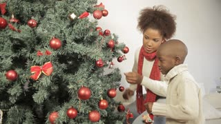 Happy boy with his mother decorating the christmas tree
