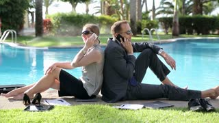 Happy business couple sitting by the poolside with cellphones