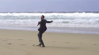 Happy businessman dancing on the beach, slow motion shot at 240fps