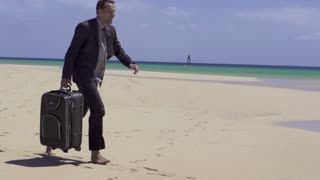 Happy businessman with suitcase down on his knees on the beach, slow motion shot