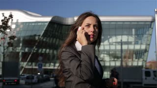 Happy businesswoman walking outside and talking on cellphone, steadycam shot