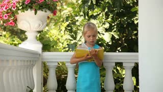 Happy child reading a book in the garden. Girl standing and holding a yellow book. Preschooler waving hand