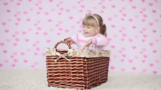 Happy child sitting in a basket