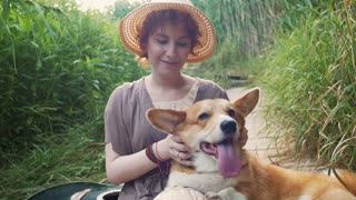 Happy corgi dog with the owner girl in the park near the reed