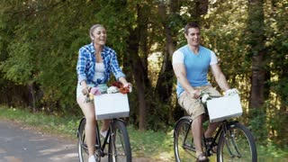 Happy couple cycling on a country road bicycle lane, steadicam shot.