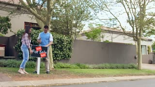 Happy couple just bought a home and hammering in sold sign board while moving in.