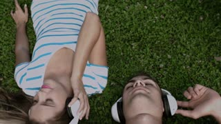 Happy couple listening to music with headphones on green grass. Above angle shot.
