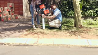 Happy couple removing sold sign board from there verge in their new home and walking into house.