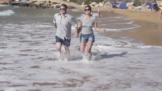 Happy couple running on the beach, slow motion shot at 480fps