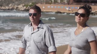 Happy couple walking on the beach, slow motion shot at 240fps