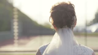 Happy European bride in elegant white wedding dress, delicate veil and with beautiful haircut, is running cross the green garden, shooting bride's back. Female wedding portrait. No people around.