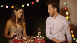 Happy excited young woman receiving a Valentines gift from a handsome young man as they enjoy a romantic meal together