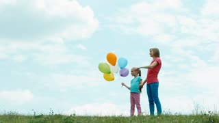 Happy family against the sky looking into the distance. Child holding balloons. Mother and daughter with balloons looking at camera. Zooming