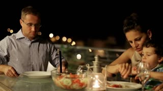 Happy family celebrating dinner on the terrace at night, steadycam shot