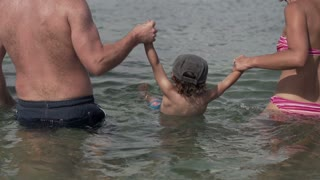 Happy family having fun in the sea, slow motion shot at 240fps