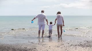 Happy family in white clothes playing on the beach